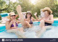 photo of mature women comp yyk three mature women sitting paddling pool drinking wine stock photo