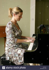 solo girl comp young blonde woman girl person playing solo piano keyboard music stock photo
